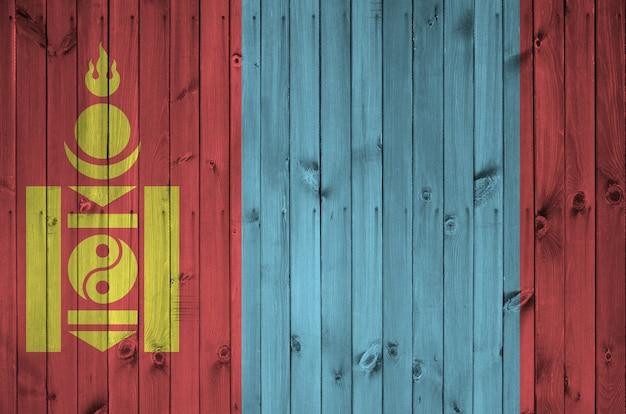 Flaga mongolii przedstawiona w jasnych kolorach farby na starej drewnianej ścianie.
