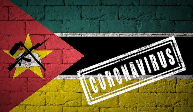 Flaga mozambiku na ceglany mur tekstury. opieczętowane koronawirusem. koncepcja wirusa koronowego. na skraju pandemii covid-19 lub 2019-ncov. nowa epidemia chińskiego koronawirusa