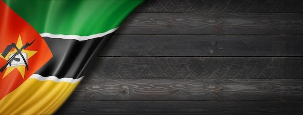 Flaga mozambiku na czarnej ścianie z drewna. poziomy baner panoramiczny.