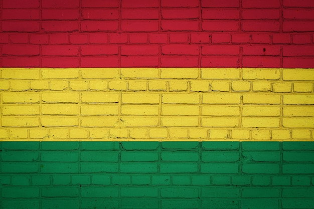 Flaga narodowa boliwii przedstawiająca na starym murem