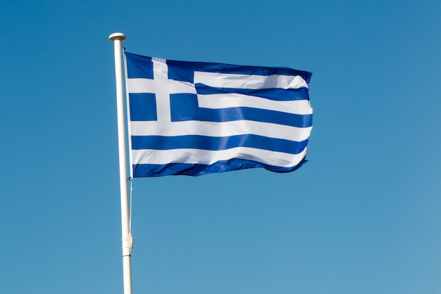 Flaga narodowa grecji na niebieskim tle nieba