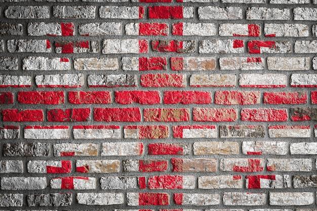 Flaga narodowa gruzji na starym ceglanym murze