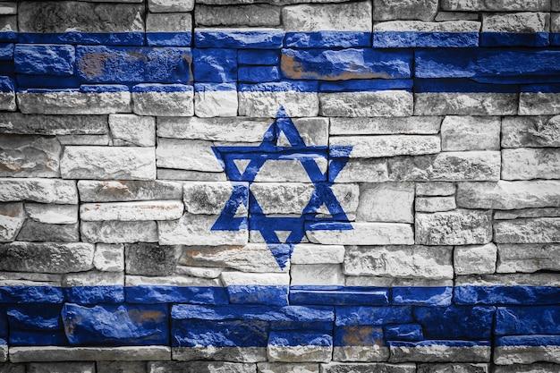 Flaga narodowa izraela na tle kamiennego muru