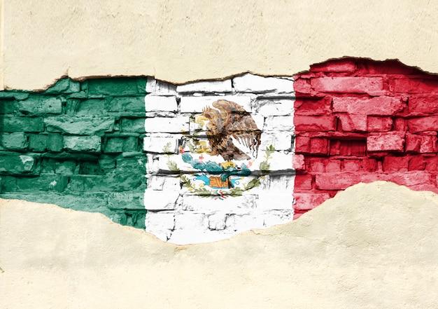 Flaga narodowa meksyku na tle cegły. mur z cegły z częściowo zniszczonym tynkiem, tłem lub teksturą.