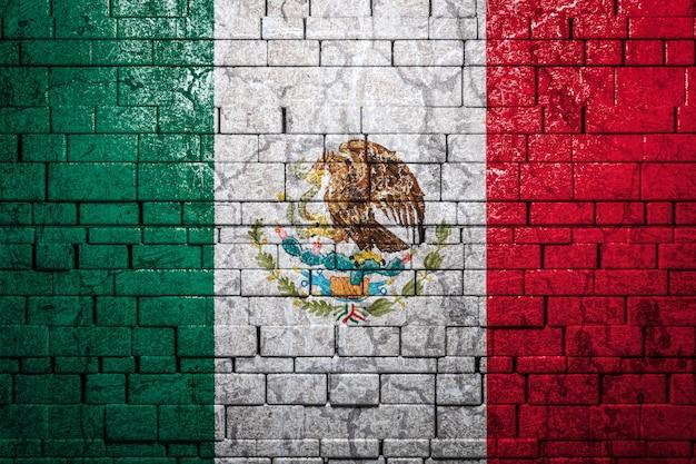 Flaga narodowa meksyku na tle ściany z cegieł.