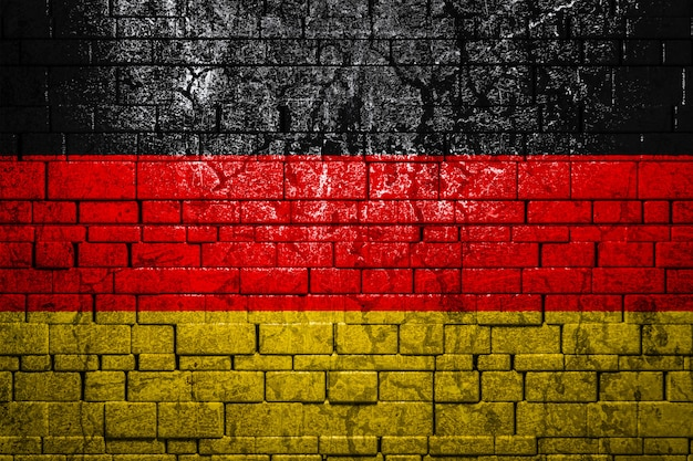 Flaga narodowa niemiec na tle ceglanego muru.