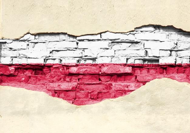 Flaga narodowa polski na tle cegły. mur z cegły z częściowo zniszczonym tynkiem, tłem lub teksturą.