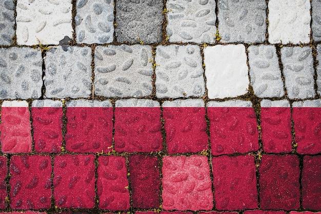 Flaga narodowa polski na tle kamiennego muru. flaga transparent na tle tekstury kamienia.