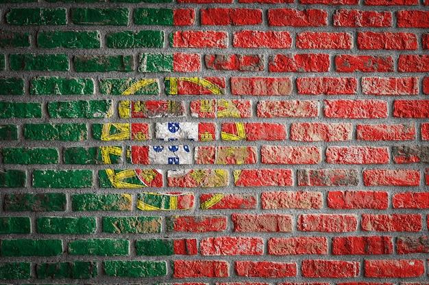Flaga narodowa portugalii na starym ceglanym murze