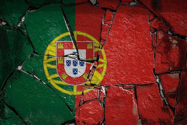 Flaga narodowa portugalii przedstawiająca w kolorach farby na starym kamiennym murze. flaga transparent na tle rozbitej ściany.