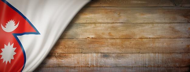 Flaga nepalu na ścianie rocznika drewna. pozioma panorama.