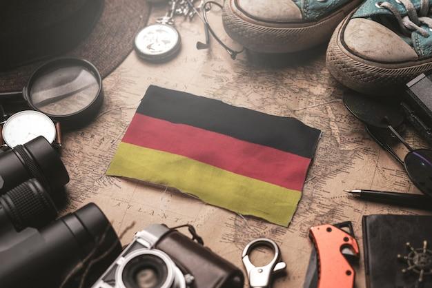 Flaga niemiec między akcesoriami podróżnika na starej mapie vintage. koncepcja miejsca turystycznego.