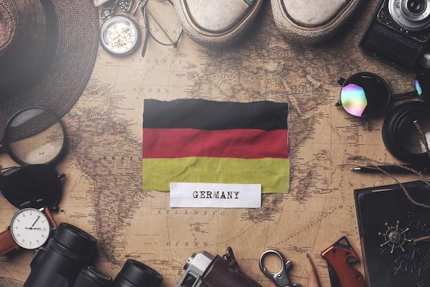Flaga niemiec między akcesoriami podróżnika na starej mapie vintage. strzał z góry