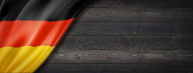 Flaga niemiec na czarnej ścianie z drewna. poziomy baner panoramiczny.