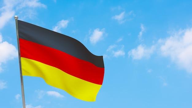 Flaga niemiec na słupie. niebieskie niebo. flaga narodowa niemiec