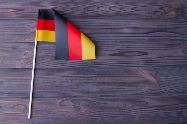 Flaga niemiec z kijem i miejscem na kopię na szarym drewnie