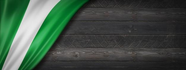 Flaga nigerii na czarnej ścianie z drewna. poziomy baner panoramiczny.