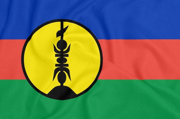 Flaga nowej kaledonii na teksturowanej tkaninie. symbol patriotyczny