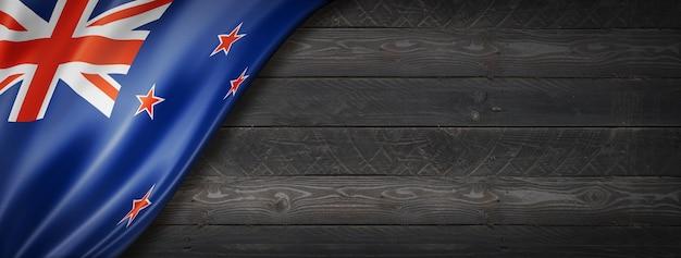 Flaga nowej zelandii na czarnej ścianie z drewna. poziomy baner panoramiczny.