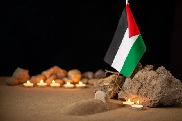 Flaga palestyny z kamieniami i płonącymi świecami na ciemnej powierzchni