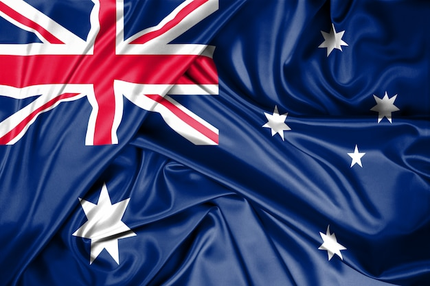 Flaga państowowa australia podnosił outdoors z niebem w tle. święto australii