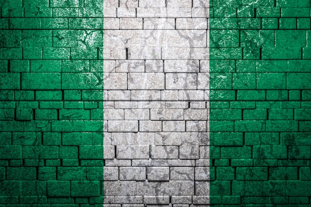 Flaga państowowa nigeria na ściana z cegieł tle.