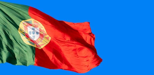 Flaga portugalii na wietrze na tle błękitnego nieba.