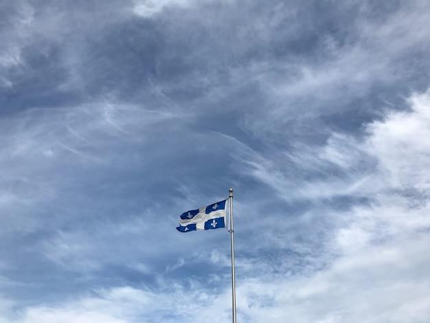 Flaga quebecu pod pięknymi chmurami na niebie