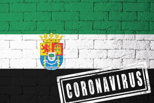 Flaga regionów lub społeczności hiszpanii estremadura o oryginalnych proporcjach. opieczętowane koronawirusem. cegła ściana tekstur. koncepcja wirusa koronowego. na skraju pandemii covid-19 lub 2019-ncov.
