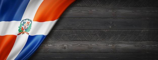 Flaga republiki dominikańskiej na czarnej ścianie z drewna