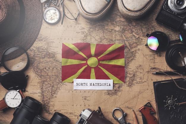 Flaga republiki macedonii między akcesoriami podróżnika na starej mapie vintage. strzał z góry