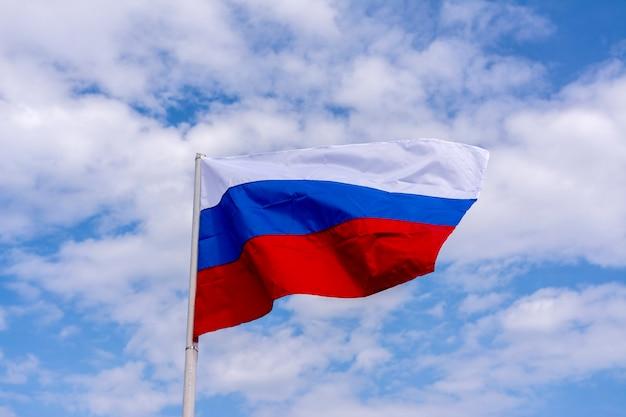 Flaga rosji powiewa na tle błękitnego nieba