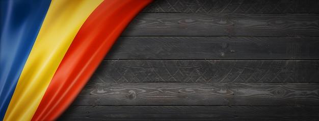 Flaga rumunii na czarnej ścianie z drewna. poziomy baner panoramiczny.