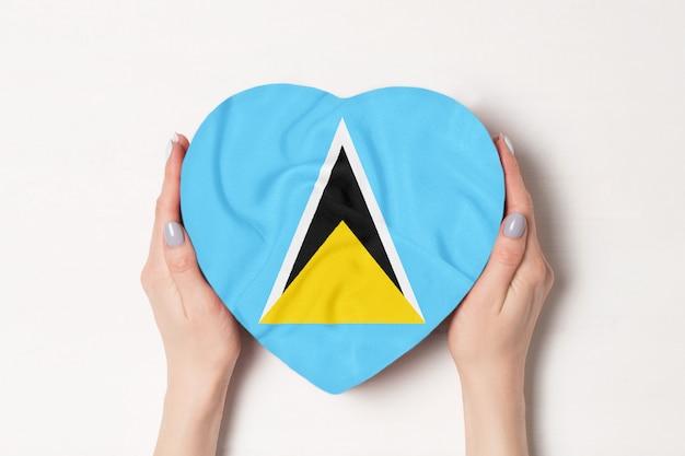 Flaga saint lucia na pudełku w kształcie serca w rękach kobiet.