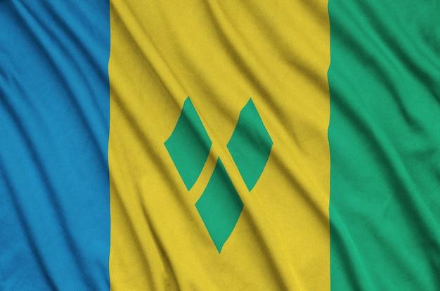 Flaga saint vincent i grenadyny jest przedstawiona na sportowej tkaninie z wieloma zakładkami.