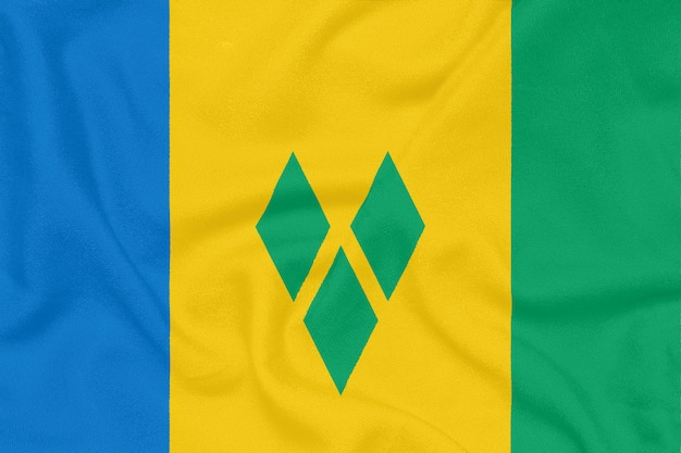 Flaga saint vincent i grenadyny na teksturowanej tkaninie. symbol patriotyczny