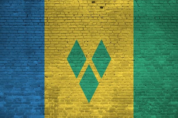 Flaga saint vincent i grenadyny w kolorach farb na starym murem. textured sztandar na dużym ściana z cegieł kamieniarstwa tle