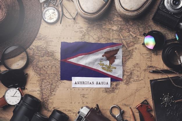 Flaga samoa amerykańskiego między akcesoriami podróżnika na starej mapie vintage. strzał z góry