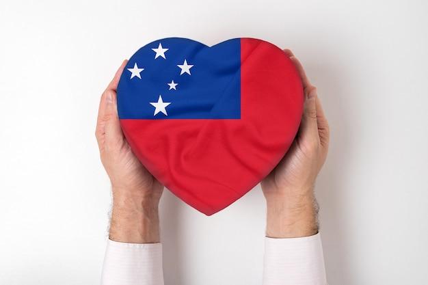 Flaga samoa na pudełku w kształcie serca w męskich rękach.