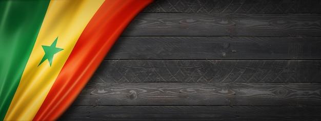Flaga senegalu na czarnej ścianie z drewna. poziomy baner panoramiczny.