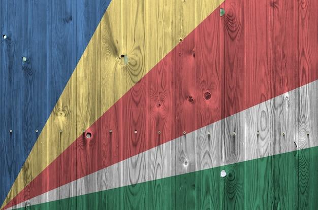 Flaga seszeli przedstawiona w jasnych kolorach farby na starej drewnianej ścianie.