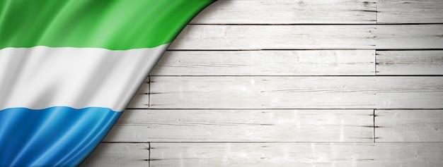 Flaga sierra leone na starej białej ścianie. poziomy baner panoramiczny.