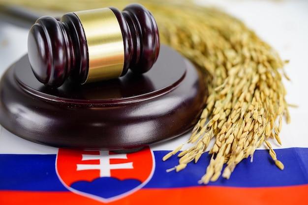 Flaga słowacji i młotek sędziego prawnika ze złotym ryżem zbożowym.