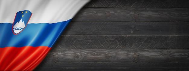 Flaga słowenii na czarnej ścianie z drewna. poziomy baner panoramiczny.