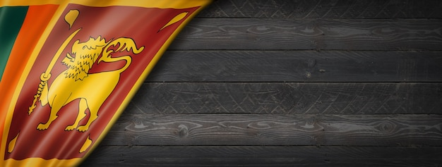 Flaga sri lanki na czarnej ścianie z drewna. poziomy baner panoramiczny.