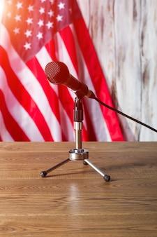 Flaga stanów zjednoczonych i mikrofon. stolik z mikrofonem obok flagi. transmisja wkrótce się rozpocznie. rano w radiu.