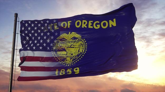 Flaga stanu oregon i usa na maszcie. flaga usa i oregonu mieszane macha na wietrze