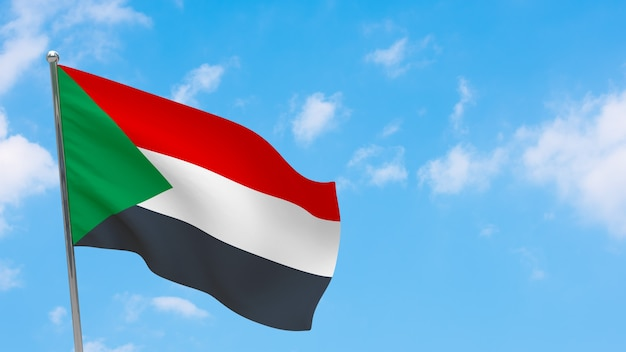Flaga sudanu na słupie. niebieskie niebo. flaga narodowa sudanu