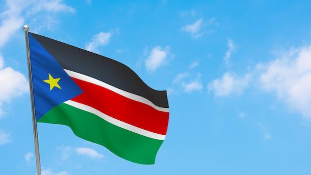 Flaga sudanu południowego na słupie. niebieskie niebo. flaga narodowa sudanu południowego