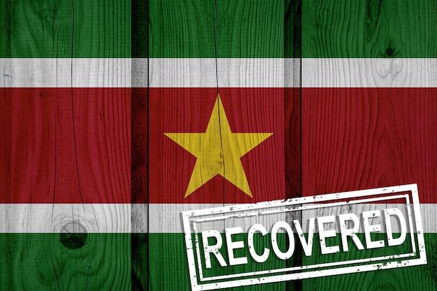 Flaga surinamu, która przeżyła lub wyzdrowiała z infekcji epidemii koronawirusa lub koronawirusa. flaga grunge z pieczęcią odzyskane